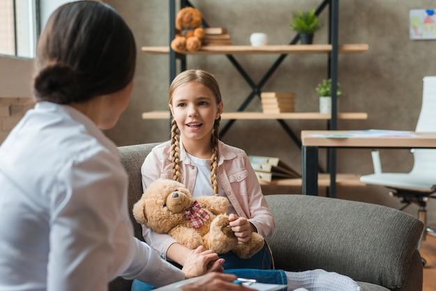 Glückliches mädchen, das zu hause mit dem weiblichen psychologen spricht