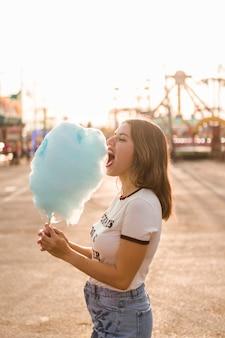 Glückliches mädchen, das zuckerwatte isst