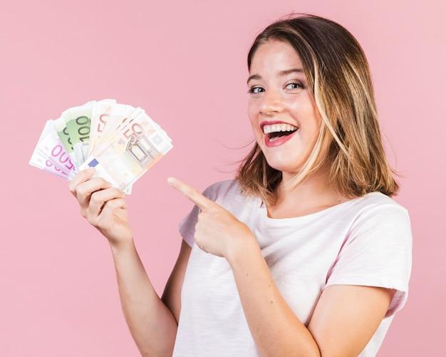 Glückliches mädchen des mittleren schusses, das geld hält