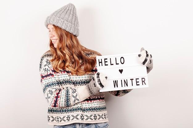 Glückliches mädchen des mittleren schusses, das hallo winterzeichen hält