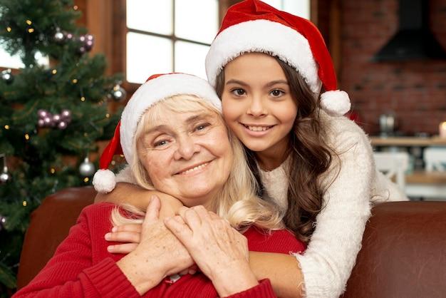 Glückliches mädchen des mittleren schusses, das ihre großmutter umarmt