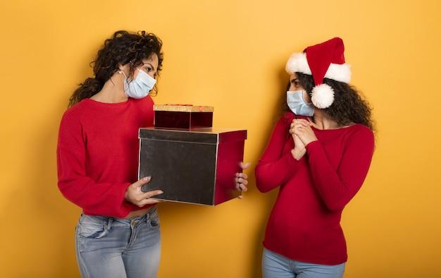Glückliches mädchen erhält weihnachtsgeschenke von einem freund auf gelb