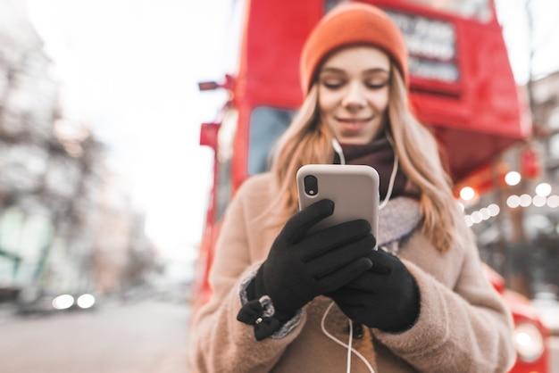 Glückliches mädchen gekleidet in warme kleidung, die auf der straße steht, musik in den kopfhörern hört und ein smartphone in handschuhen benutzt