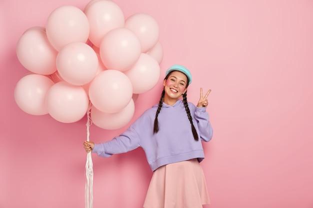 Glückliches mädchen grüßt freunde auf ballonparty, hat zwei zöpfe, trägt lila pullover und rock, macht friedensgeste, steht gegen rosa wand