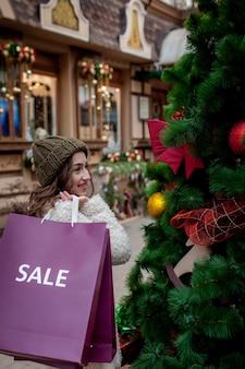 Glückliches mädchen hält papiertüten mit symbol des verkaufs in den geschäften mit verkäufen zu weihnachten