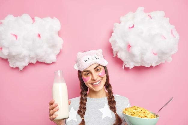 Glückliches mädchen hat ein gesundes frühstück, hält eine schüssel mit müsli und frische milch lächelt angenehm und hat teo-zöpfe im pyjama
