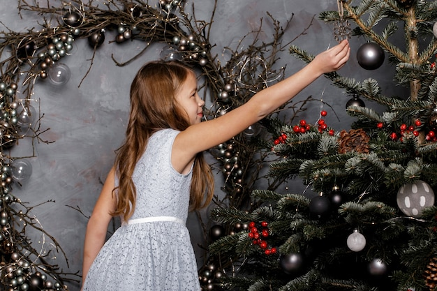 Glückliches mädchen im blauen kleid, das weihnachtsbaum verziert.