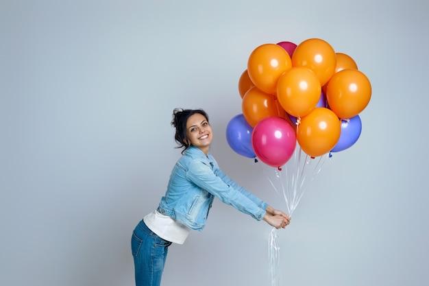 Glückliches mädchen im denim, das mit hellen bunten luftballons auf grau isoliert aufwirft