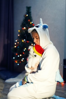 Glückliches mädchen im einhornkostüm mit samojede-husky-hund in weihnachtsdekoration