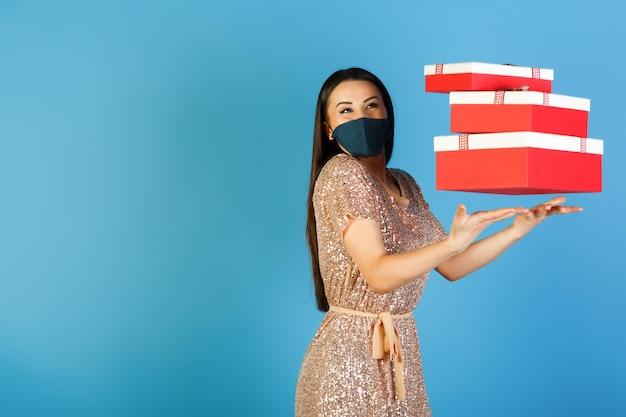 Glückliches mädchen im eleganten kleid und in der schutzmaske wirft geschenke auf, die auf blauem hintergrund mit leerem raum für ihren text lokalisiert werden.