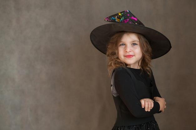 Glückliches mädchen im halloween-hexenkostüm auf grauem hintergrund