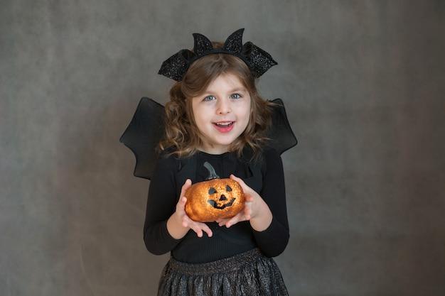 Glückliches mädchen im halloween-kostüm mit kürbis auf grauem raum