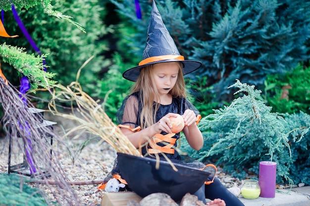 Glückliches mädchen im halloween-kostüm mit steckfassungskürbis. süßes sonst gibt's saures