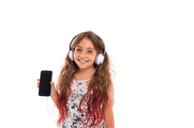 Glückliches mädchen im prickelnden kleid, wenn die großen weißen kopfhörer musik hören und schirm des schwarzen smartphone lokalisiert sind