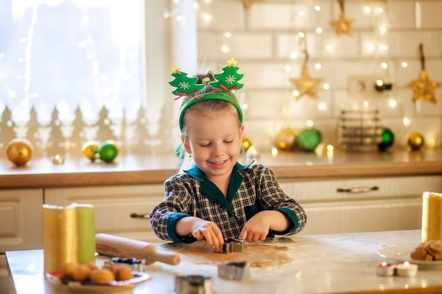 Glückliches mädchen im pyjama, das den teig für neujahrsplätzchen vorbereitet, um weihnachten zu feiern.