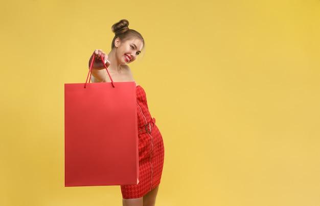 Glückliches mädchen im roten kleid, das rote einkaufstasche lokalisiert auf gelber wand hält