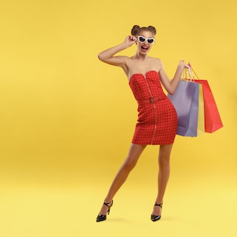 Glückliches mädchen im roten kleid und in der sonnenbrille, die bunte einkaufstaschen auf gelber wand halten