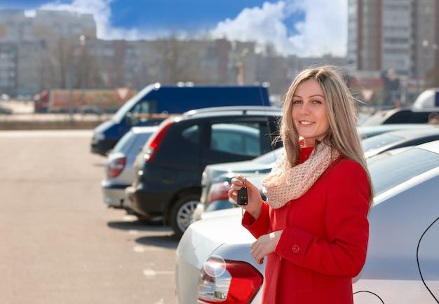 Glückliches mädchen im roten mantel mit den schlüsseln der autos auf dem parkplatz