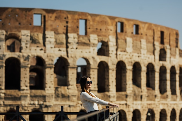 Glückliches mädchen im weißen hemd mit der lächelnden brille und bewundert das kolosseum von rom.