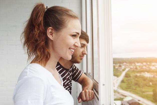 Glückliches mädchen im weißen t-shirt und kerl mit bart, niedliches paar, das aus dem fenster in ihrem neuen zuhause schaut