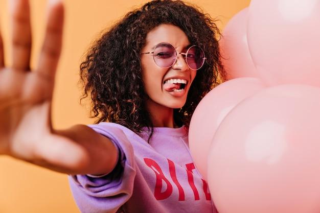 Glückliches mädchen in der runden lila brille, die lustige gesichter macht. raffinierte afrikanische dame mit dunklem haar, das auf orange aufwirft.