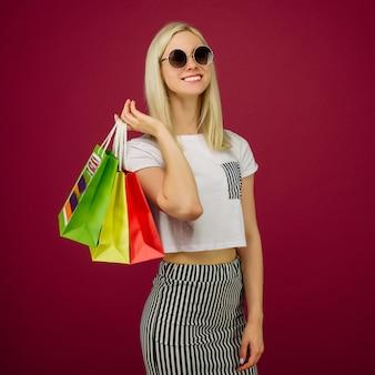 Glückliches mädchen in der sonnenbrille hält einkaufstaschen auf rubin