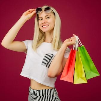 Glückliches mädchen in der sonnenbrille hält einkaufstaschen