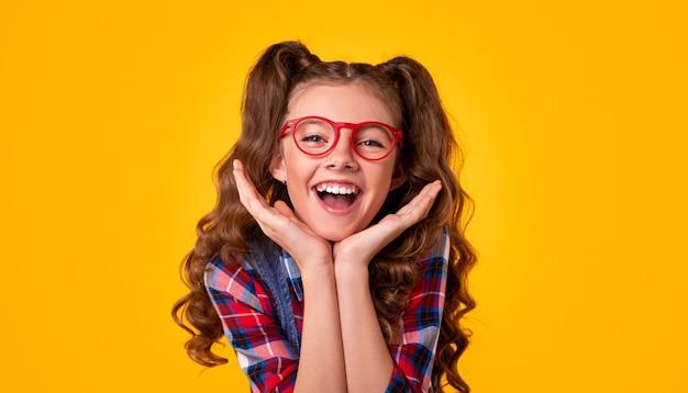 Glückliches mädchen in der stilvollen brille und im karierten hemd, die gesicht berühren und schauen