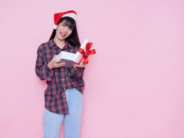 Glückliches mädchen in der weihnachtsmannmütze, die eine geschenkbox gegen rosa wand öffnet