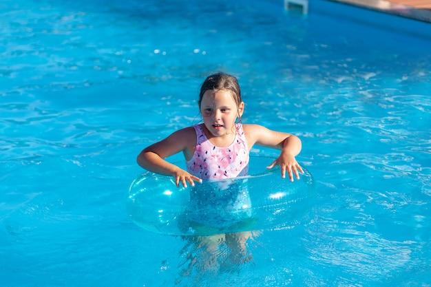 Glückliches mädchen in einem aufblasbaren kreis zum schutz im wasser lernen, in der hotelpoolruhe zu schwimmen ...