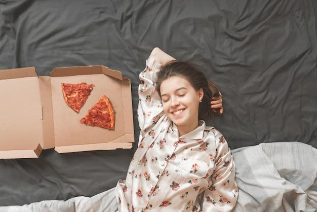 Glückliches mädchen in einem pyjama liegt auf einem bett mit einer schachtel pizza und lächelt.