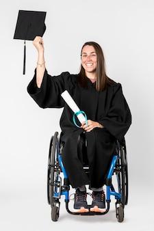 Glückliches mädchen in einem rollstuhl, das ihr diplom hält
