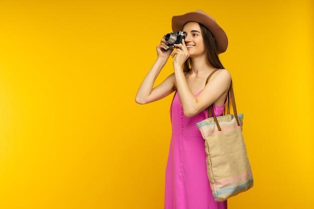 Glückliches mädchen in einem rosa kleid und in der sonnenbrille, die kamera auf einem gelben bild halten