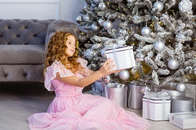 Glückliches mädchen in einem weihnachtskleid, das die geöffnete geschenkbox, weihnachtszeitkonzept hält.