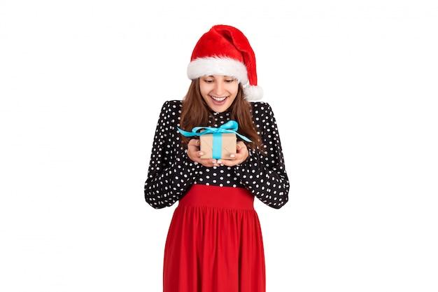 Glückliches mädchen in einem weihnachtsmann-hut freut sich, ein geschenk zu erhalten. isoliert