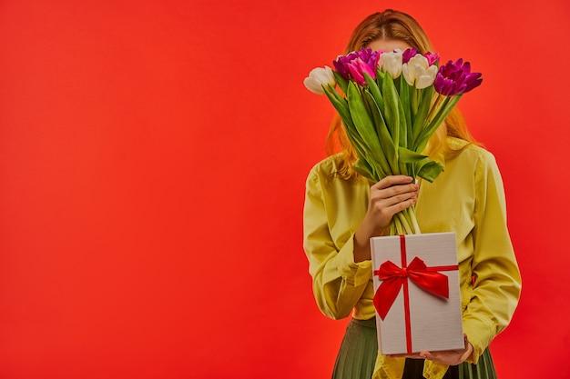 Glückliches mädchen in einer gelben bluse spielen mit einem strauß tulpen und zeigt eine weiße schachtel, die mit rotem band gebunden wird