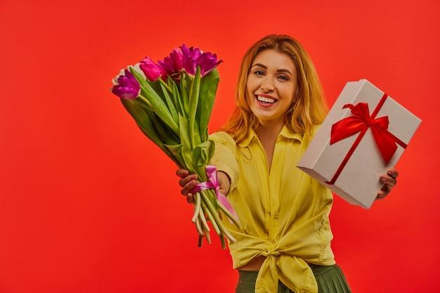 Glückliches mädchen in einer gelben bluse zeigt und umarmt einen strauß tulpen und eine geschenkbox, die mit rotem band an die kamera gebunden wird