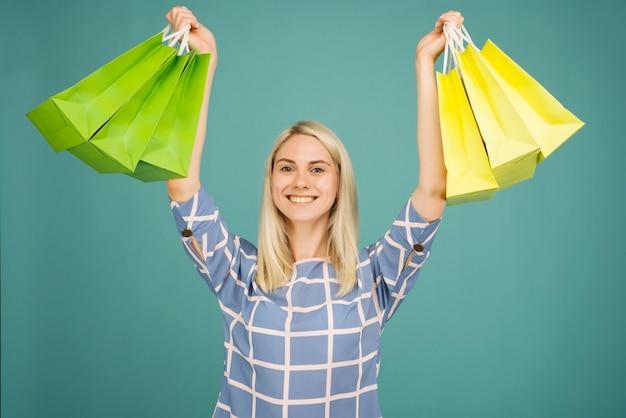 Glückliches mädchen in einer karierten bluse hält einkaufstaschen auf blau
