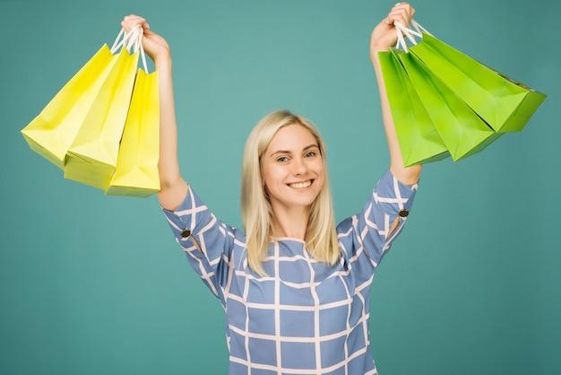 Glückliches mädchen in einer karierten bluse hält einkaufstaschen auf blauem hintergrund