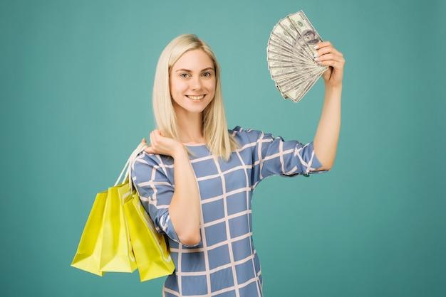 Glückliches mädchen in einer karierten bluse hält hundert dollarscheine und einkaufstaschen