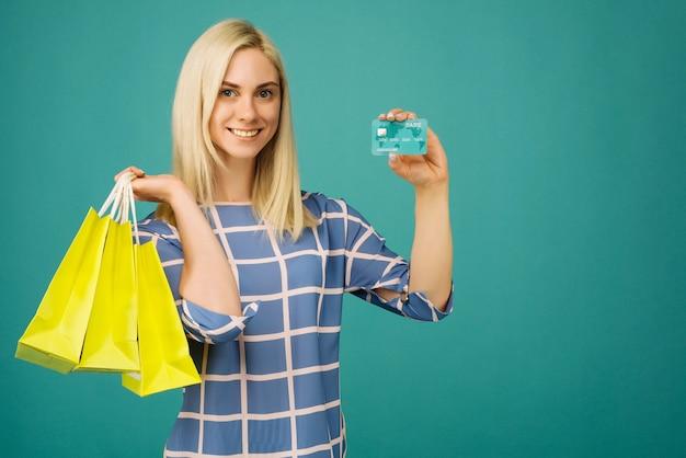 Glückliches mädchen in einer karierten bluse hält kreditkarte und einkaufstaschen auf blau