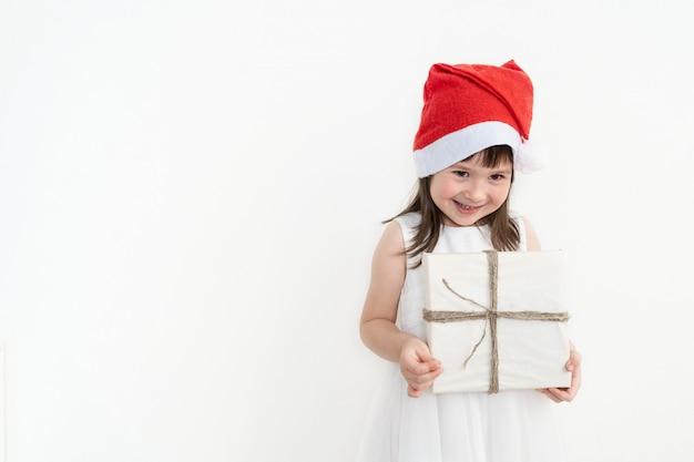 Glückliches mädchen in einer roten kappe. das kind hält eine schachtel mit einem geschenk in einer umweltfreundlichen verpackung.