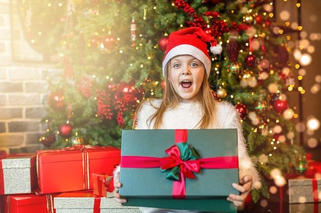 Glückliches mädchen in einer weihnachtsmütze wird von einer magischen geschenkbox auf dem weihnachtsbaumhintergrund überrascht. frohe weihnachten