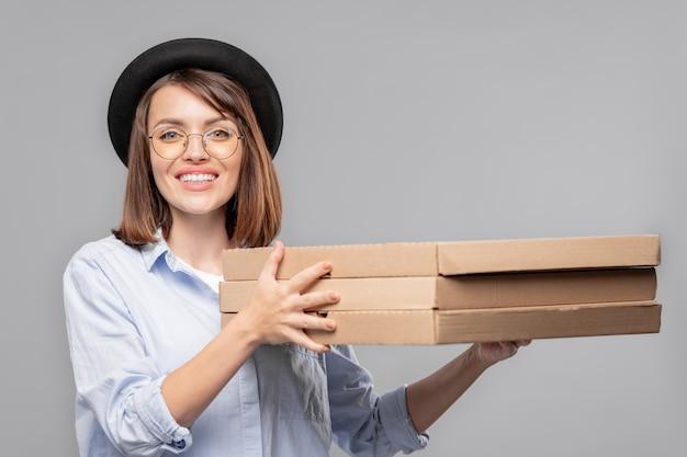 Glückliches mädchen in hut, hemd und brille, die stapel von dünnen kartonverpackungen oder geschenkboxen isoliert halten