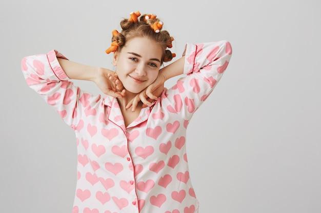 Glückliches mädchen in pyjamas und lockenwicklern, die sich nach dem aufwachen dehnen