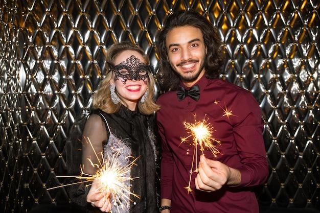 Glückliches mädchen in venezianischer maske und kerl mit funkelnden bengalischen lichtern, die gegen wand im nachtclub vor kamera stehen