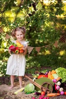 Glückliches mädchen kocht gemüsesalat auf der natur. ein kleiner gärtner sammelt eine ernte gemüse.
