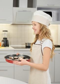 Glückliches mädchen lächelnd, backform mit keksen haltend.
