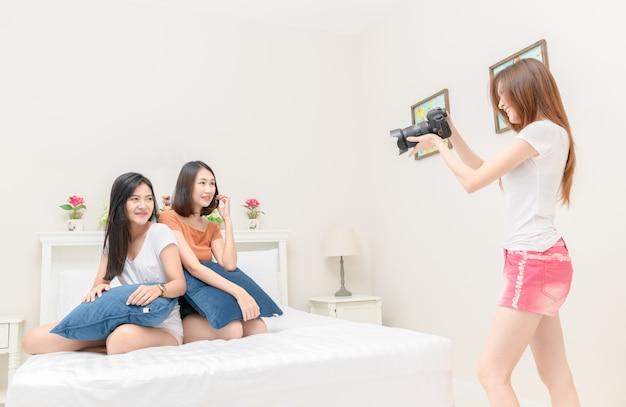 Glückliches mädchen machen foto durch kamera im schlafzimmer