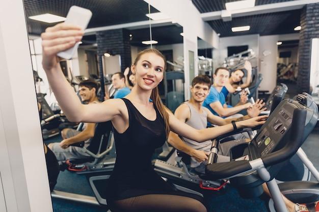 Glückliches mädchen macht allgemeines gruppenfoto am training